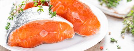 Fresh raw salmon fish steaks on white kitchen background. Banner