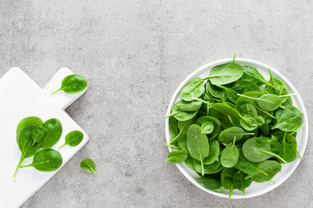 Fresh spinach leaves on white plate. Healthy vegan food. Top view Reklamní fotografie - 118170485