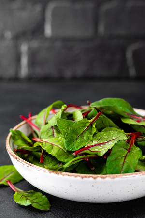 Fresh chard leaves on black background