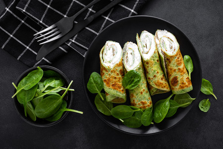 Savory crepes with spinach and feta cheese on black background, top view Banco de Imagens - 118170855