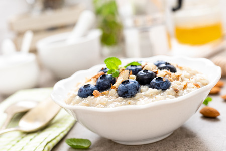 Oatmeal with fresh blueberry, almond nuts and honey for breakfast Stock Photo - 118170960