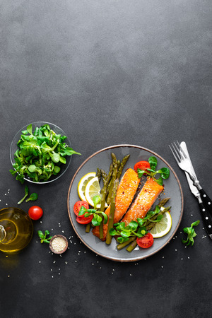 Grilled salmon fish steak, asparagus, tomato and corn salad on plate. Healthy dish for lunch. Top view Archivio Fotografico