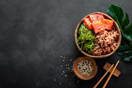 Bol de poke avec du poisson saumon cru, de la salade de chuka et du riz dans des bols de noix de coco sur fond noir Banque d'images