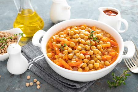 Chana Masala, spicy chickpea curry with carrot and onion in tomato sauce. Vegetarian dish for lunch. Indian cuisine