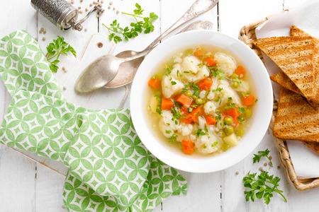 Gemüsesuppe mit Blumenkohl, Karotten, grünen Erbsen, Zwiebeln und Kartoffeln