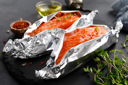 Raw salmon fish fillet in foil on black background