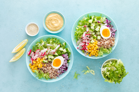 Buddha bowl with boiled egg, rice and vegetable salad of fresh lettuce, radish, cucumber, corn, onion and sesame seeds and chickpea sauce