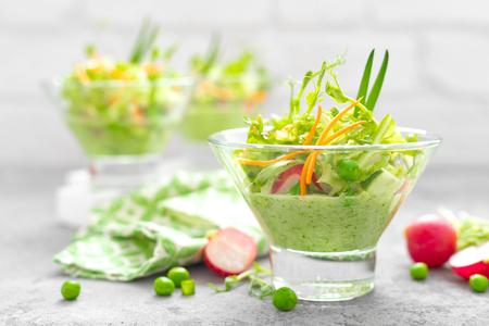 Ensalada de vegetales frescos veganos con zanahoria, lechuga, guisantes, rábano, brotes y batido de pepino Foto de archivo