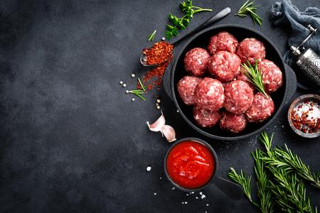 Frische rohe Rindfleischbällchen mit Gewürzen und Tomatensauce