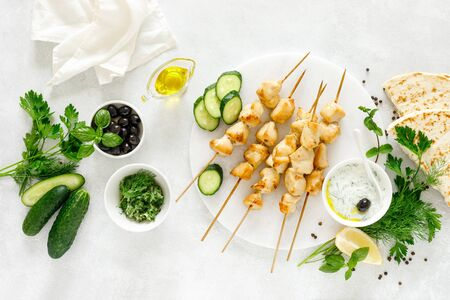 Grilled chicken kebab on skewers and traditional Greek tzatziki yogurt sauce, tview from above Фото со стока