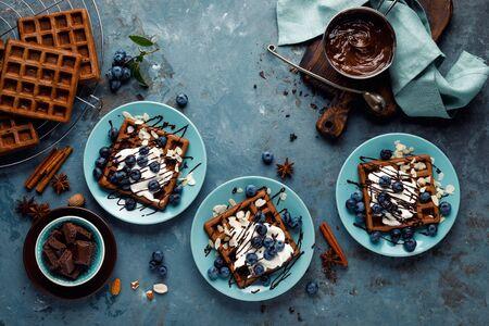 Gaufres belges au chocolat avec crème glacée et myrtilles fraîches sur fond bleu, vue de dessus