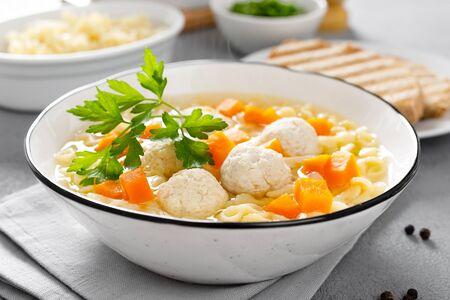 Zuppa di pollo calda, brodo con polpette, carota, pasta e prezzemolo fresco