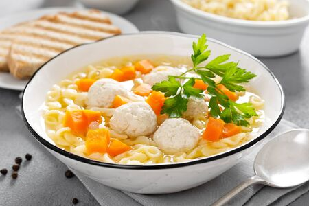 Hot chicken soup, broth with meatballs, carrot, pasta and fresh parsley