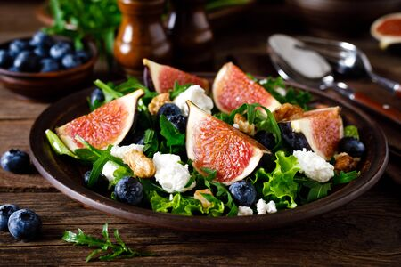 Fig salad with goat cheese, blueberry, walnuts and arugula on wooden background. Healthy food. Lunch Фото со стока