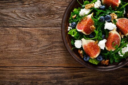 Fig salad with goat cheese, blueberry, walnuts and arugula on wooden background. Healthy food. Top view Фото со стока