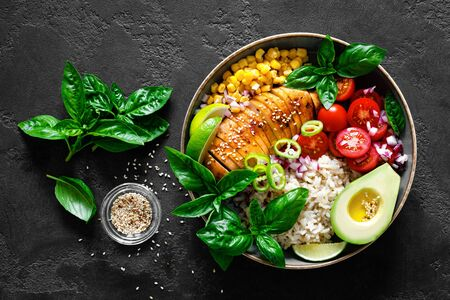 Grilled chicken breast lunch bowl with fresh tomato, avocado, corn, red onion, rice and basil Фото со стока