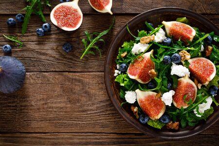 Feigensalat mit Ziegenkäse, Blaubeere, Walnüssen und Rucola auf Holzhintergrund. Gesundes Essen. Ansicht von oben
