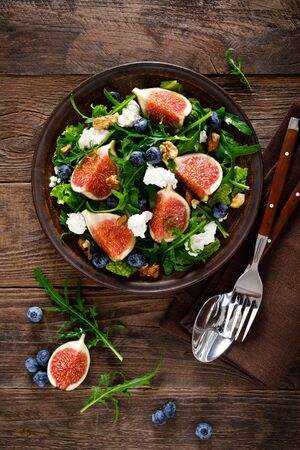 Fig salad with goat cheese, blueberry, walnuts and arugula on wooden background. Healthy food. Top view Фото со стока - 128551064