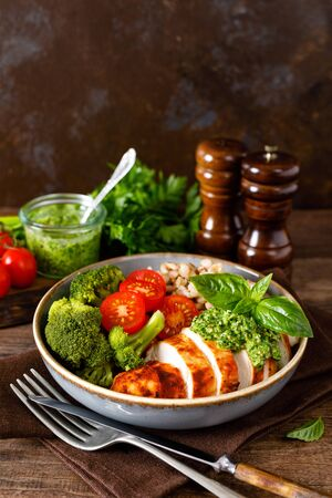 Chicken lunch bowl with broccoli, fresh tomato, pearl barley porridge and basil pesto on wooden rustic background Фото со стока
