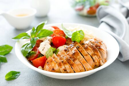 Grilled chicken lunch bowl with orange juice dressing, pasta and caprese salad Фото со стока