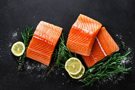 Salmon. Fresh raw salmon fish fillet with cooking ingredients, herbs and lemon on black background, top view Фото со стока - 128702064