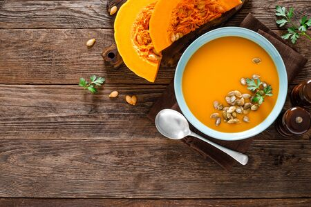 Pumpkin soup. Vegetarian soup with pumpkin seeds in bowl on wooden table, top view Фото со стока - 128702056