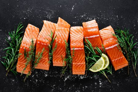 Salmon. Fresh raw salmon fish fillet with cooking ingredients, herbs and lemon on black background, top view Фото со стока - 128702069