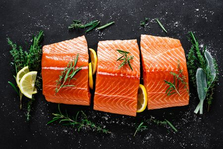 Salmon. Fresh raw salmon fish fillet with cooking ingredients, herbs and lemon on black background, top view Фото со стока