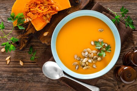 Pumpkin soup. Vegetarian soup with pumpkin seeds in bowl on wooden table, top view Фото со стока - 128702196