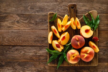 Peaches. Sliced ripe peaches with leaves on wooden board, top view