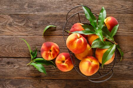 Ripe peaches with leaves in basket on wooden table, top view
