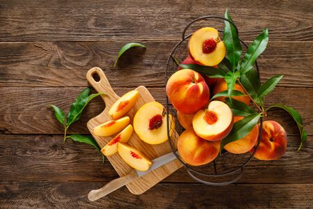 Ripe peaches with leaves in basket on wooden table, top view Фото со стока
