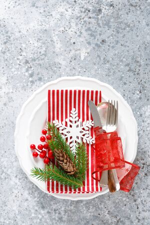 Christmas table setting with empty festive white plate and cutlery with Xmas decorations, snowflake, cone, Xmas tree branches and New Year napkin. Holiday food background with copy space for text