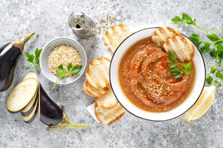 Eggplant hummus with ingredients for cooking. Traditional vegan arabic aubergine appetizer. Baba Ghanoush Фото со стока - 128906031