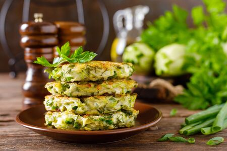 Vegetable fritters with zucchini and greens Фото со стока - 128906050