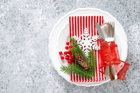 Christmas table setting with empty festive white plate and cutlery with Xmas decorations, snowflake, cone, Xmas tree branches and New Year napkin. Holiday food background with copy space for text Фото со стока - 128906179