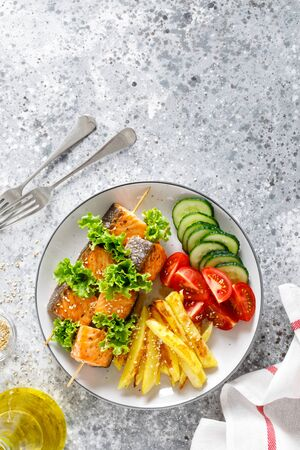 Grilled salmon kebab on skewers with baked potato, fresh cucumbers and tomatoes