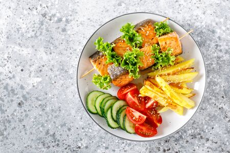 Grilled salmon kebab on skewers with baked potato, fresh cucumbers and tomatoes Фото со стока - 128906225