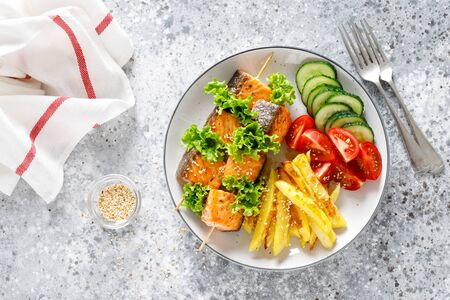 Grilled salmon kebab on skewers with baked potato, fresh cucumbers and tomatoes Фото со стока - 128906230