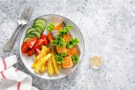 Grilled salmon kebab on skewers with baked potato, fresh cucumbers and tomatoes Фото со стока - 128906228