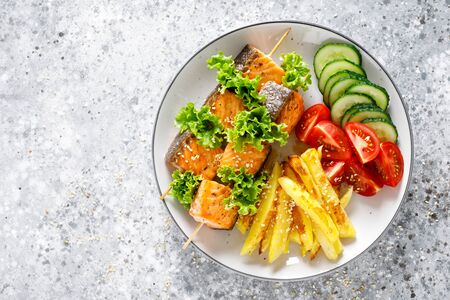 Grilled salmon kebab on skewers with baked potato, fresh cucumbers and tomatoes Фото со стока - 128906245