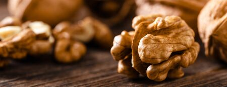 Walnuts. Kernels and whole nuts on wooden rustic table closeup, banner Stock fotó