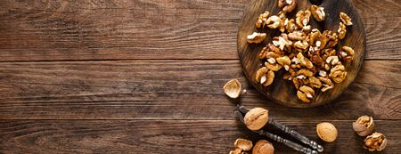Walnuts. Kernels and whole nuts on wooden rustic table, banner, top view