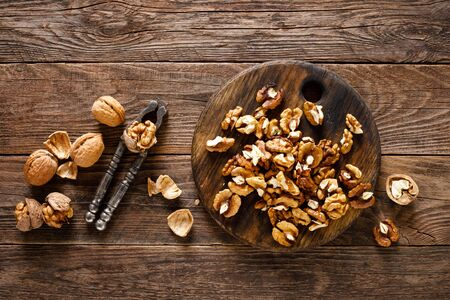 Walnuts. Kernels and whole nuts on wooden rustic table, top view