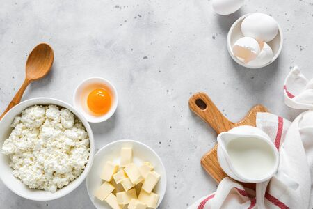 Pitcher with milk, egg, cottage cheese, butter and yogurt on kitchen table. Ingredients for cooking on kitchen table with copy space. Culinary background. Top view. Flat lay