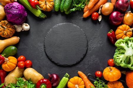 Culinary background with fresh raw vegetables on a black kitchen table, healthy vegetarian food concept, flat lay composition, top view Banco de Imagens