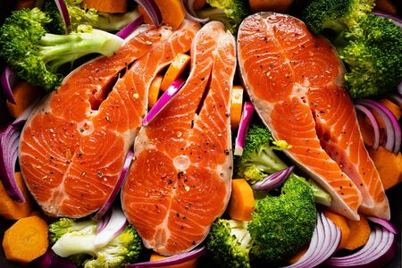 Salmon. Cooking fresh raw salmon fish steaks with vegetables, broccoli, carrot and onion on black 免版税图像
