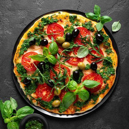 Pizza. Pizza italiana tradicional con salsa pesto de albahaca verde, vista superior Foto de archivo