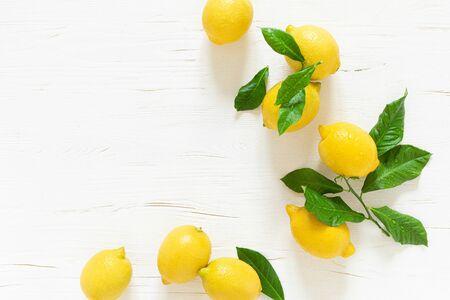 Fresh lemons with leaves on white wooden background,  summer lemonade ingredient, vitamin c concept, top view  Reklamní fotografie