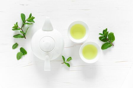 Green mint tea with fresh leaves in cups and teapot overhead on white wooden table, healthy warming drink, antioxidant beverage, top view